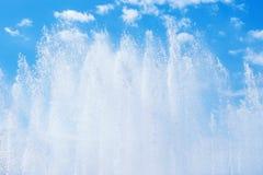 Brunnen, der Jets gegen blauen bewölkten Himmel spritzt Stockfotografie