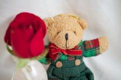 Brunnen gekleideter adretter kleiner Teddy Bear mit einer roten Rose für die Feiertage oder die Feiern Stockfotos