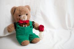 Brunnen gekleideter adretter Teddy Bear mit einer roten Rose für die Feiertage oder die Feiern Lizenzfreies Stockfoto