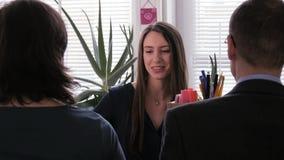 Brunnen getan - zufriedene Geschäftsfrau gibt ihrem Team ein Klemmbrett mit einem Projekt