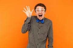Brunnen hallo! Lächelnde des jungen erwachsenen verrückten Mannes toothy und darstellende Hand a stockfotos