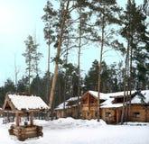 Brunnen und ein Blockhaus in einem Kiefernwald nahe dem Dorf von Arkhangelsk (Russland-, Ulyanovsk-Region) an einem Wintertag Lizenzfreie Stockfotos