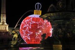 Brunnen und eine riesige Rot-Weihnachtskugel mit weißen Sternen Lizenzfreie Stockfotografie