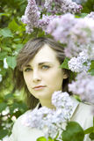 Brunnete woman standing nearby lilac. Royalty Free Stock Photos
