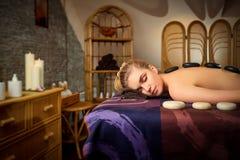 Brunnsort för stenmassage tillbaka för en kvinna i skönhetmitten arkivfoto
