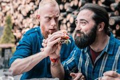 Bruno barbuto che ritiene stupefacente dopo il morso deun certo hamburger immagini stock libere da diritti