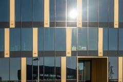 Brunswick, Alemania, el 17 de noviembre , 2018: Reflexión del sol en un edificio moderno con una fachada del vidrio y del hormigó imagenes de archivo