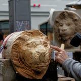 Brunswick, Nedersaksen, Duitsland, 27,2018 Januari: De kunstenaar snijdt het hoofd van een leeuw van een brok van hout, het emble Stock Afbeelding