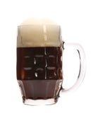 Brunt öl med skum rånar in. Royaltyfri Foto
