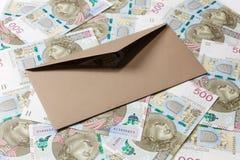 Brunt öppnat kuvert på bakgrund för 500 PLN-sedlar arkivfoto