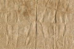 Brunt ark för tappning av papper med talrika veck och sprickor på yttersida, abstrakt bakgrund av skrynkligt papper Fotografering för Bildbyråer