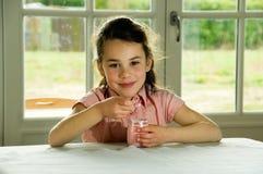 brunt barn som äter haired yoghurt arkivbild