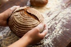 Brunt bröd i händer Royaltyfri Fotografi