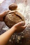 Brunt bröd i händer Fotografering för Bildbyråer