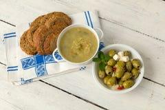 Brunt bröd med soppa och oliv Arkivfoto