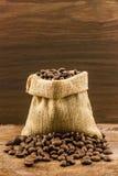 Brunt grillade kaffebönor i kanfassäck Arkivfoton