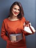Brunt hår som ler flickan med gåvan i hjärtaform Arkivfoto