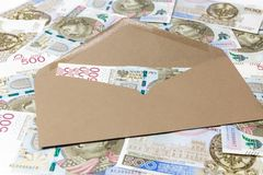 Brunt kuvert med 500 PLN-sedlar på sedelbakgrund royaltyfria bilder