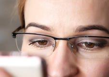Brunt kvinnaöga för närbild i exponeringsglas Kvinna som använder en smartphone royaltyfria foton