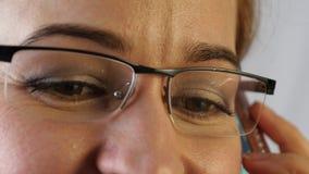Brunt kvinnaöga för närbild i exponeringsglas Kvinna som använder en smartphone 4K lager videofilmer