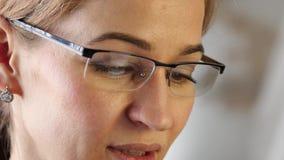 Brunt kvinnaöga för närbild i exponeringsglas Kvinna som använder en smartphone 4K stock video