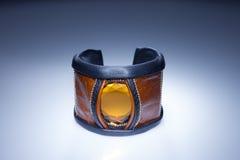 Brunt läderarmband med den gula stenen Arkivbild