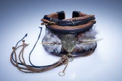 Brunt läderarmband med metallhängen och fjädrar Arkivfoto
