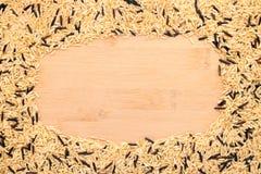 Brunt och lösa blandade ris som inramas på en bambu Royaltyfri Bild