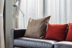 Brunt och röd kudde på den moderna soffan med lampan Royaltyfri Bild