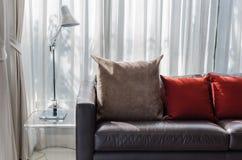 Brunt och röd kudde på soffan med lampan Fotografering för Bildbyråer
