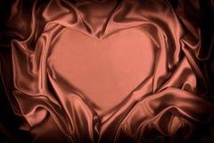 Brunt silke vek hjärtaform som var användbar för bakgrunder Arkivfoton