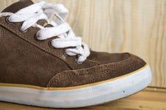 Brunt skor slitet på bakgrunden av trä Royaltyfri Bild