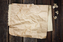 Brunt skrynkligt papper på wood bakgrund Royaltyfria Bilder