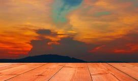 Brunt träbräde över härlig solnedgång med berget royaltyfri fotografi