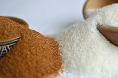 Brunt vs. vitsocker. Två variants av socker i bunkar. Arkivbilder