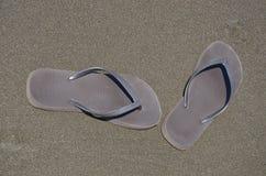 Bruntet parar av flipmisslyckande skor på den bruna sanden Fotografering för Bildbyråer