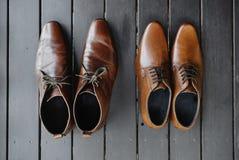 Bruntskorna på det svarta trägolvet, läder arkivfoton