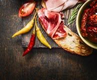 Bruschetta或crostini用意大利火腿和开胃小菜在黑暗的木背景, 免版税库存照片