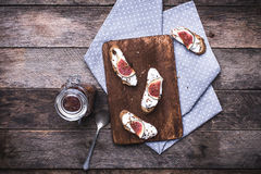 Bruschetta用乳脂干酪和无花果在砧板在rusti 库存图片