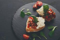 Bruschetta用乳酪和菜在黑背景 免版税库存照片