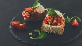 Bruschetta用乳酪和菜在黑背景 免版税库存图片
