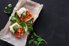 Bruschetta用乳酪和菜在黑背景 库存图片