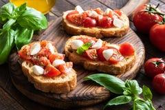 Bruschetta用在木板的蕃茄、蓬蒿和无盐干酪乳酪 库存照片