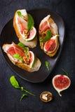 Bruschetta用山羊乳干酪、无花果、熏火腿和芝麻菜 免版税图库摄影