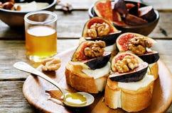 Bruschetta用无花果、蜂蜜、山羊乳干酪和核桃 免版税图库摄影