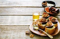 Bruschetta用无花果、蜂蜜、山羊乳干酪和核桃 免版税库存图片