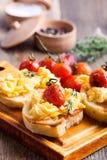 Bruschetta用炒蛋和烤西红柿 库存照片