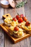 Bruschetta用炒蛋和烤西红柿 库存图片