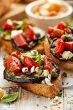 Bruschetta用烤茄子、西红柿、希腊白软干酪、雀跃和新鲜的芳香草本在一张木桌上 可口Medit 库存图片