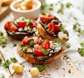 Bruschetta用烤茄子、西红柿、希腊白软干酪、雀跃和新鲜的芳香草本在一张木桌上 可口Medit 免版税图库摄影
